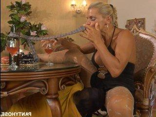 Голые блондина с большой грудью сосет хуй, лежа на столе